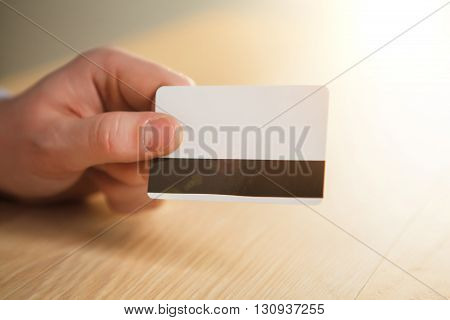 The male hand showing credit card on the background of table