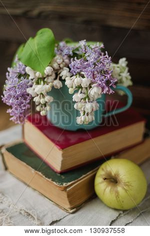 Two old books apple and rusty mug with lilac bouquet on homespun napkin. Interesting reading vintage background.