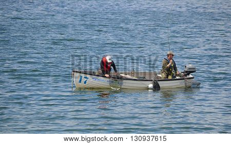 Grafham, Cambridgeshire, England - May 22, 2016: Two fisherman fishing with rods in boat.