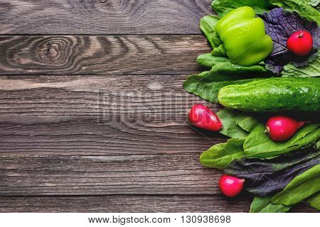 Fresh ingredients for salad - sorrel leaves radishes cucumber sweet pepper on wooden background. Rustic table with tasty vegetables. Place for text.