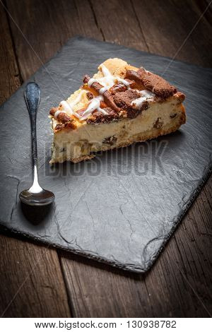 Cheesecake With Raisins On A Slate Plate.