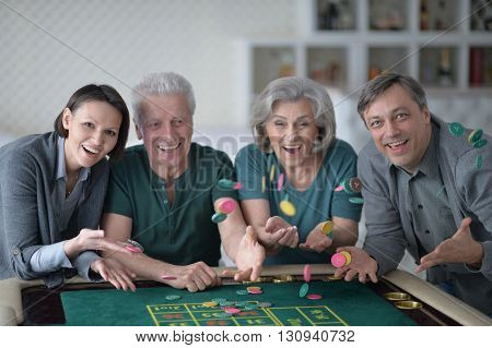 Happy family with senior couple playing with casino chips