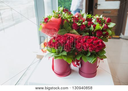 Beautiful bouquets of red roses in gift box, on white windowsill, delivery service