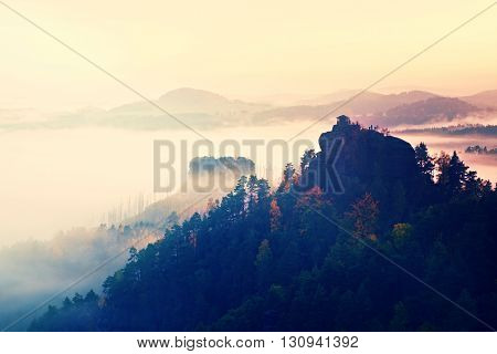 Cold Misty Daybreak In A Fall Valley Of Bohemian Switzerland Park. Hill With Hut On The Peak Increas