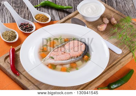 Hearty salmon soup on a white plate with spices hot pepper and cream sauce served on an orange table napkin at the rustic wooden table close-up