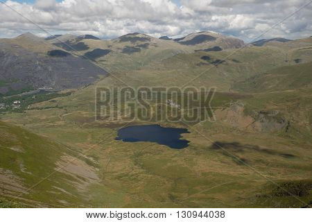 Lake Llyn Dwythwch nestled in a grassy valley above Llanberis with the Glyder mountain range in the distance Snowdonia Wales UK.
