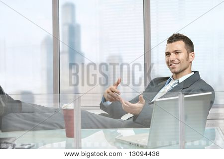 Relaxed businessman  sitting at desk in front of office windows, talking to somebody.