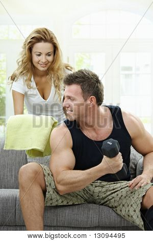 Muscular man sitting on sofa at home, doing excercise with hand barbell, her girlfriend bringing towel.