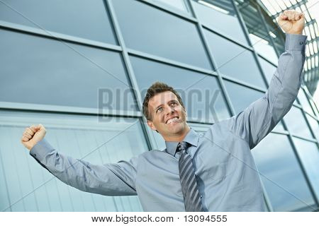 Happy successful businessman raising arms outdoor, smiling.