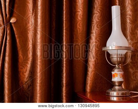 Old lamp on a furniture with velvet curtain in background