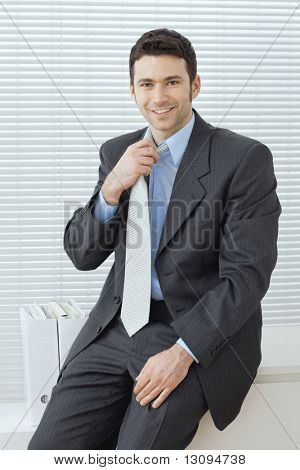 Businessman wearing grey suit and blue shirt, sitting in office, adjusting his tie, smiling.