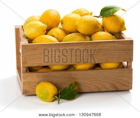 Lemons with green leaves in a crate with one on the surface in the foreground isolated on white background.
