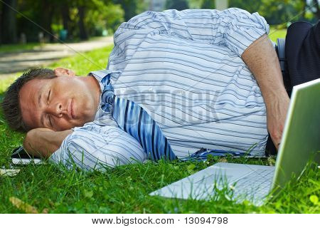 Closeup portrait of relaxed businessman lying in grass beside laptop computer.
