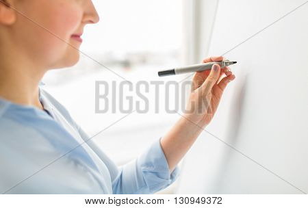 office, business, people and education concept - close up of woman with marker writing or drawing something on white board