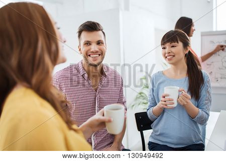 business, startup and people concept - happy creative team or students drinking coffee and talking at office