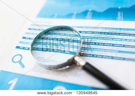 business, statistics, economy, finance and research concept - close up of financial report document and magnifying glass