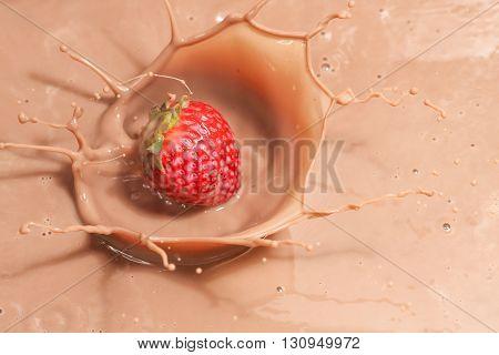 closeup of strawberry splashing into chocolate milk