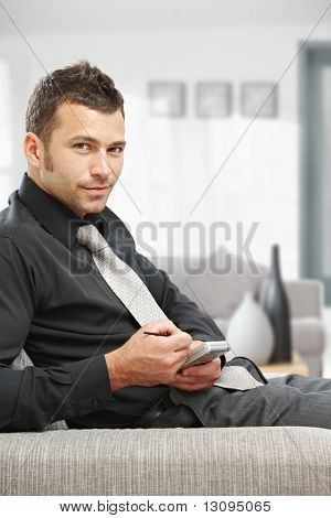 Young businessman sitting on sofa at office lobby using palmtop organizer.