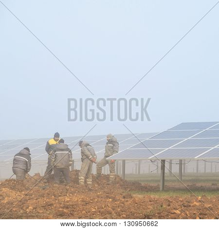 MANSFIELD WOODHOUSE ENGLAND - MARCH 13: Workmen working at a solar energy farm currently under construction. In Mansfield Woodhouse Nottinghamshire England. On 13th March 2016.