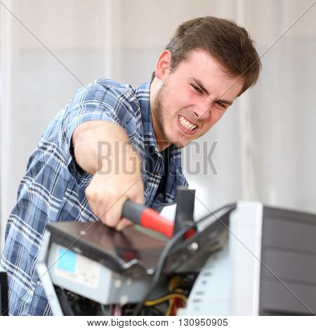 Portrait of furious and crazy man without self control hitting a computer with a hammer hating technology problems in office or home