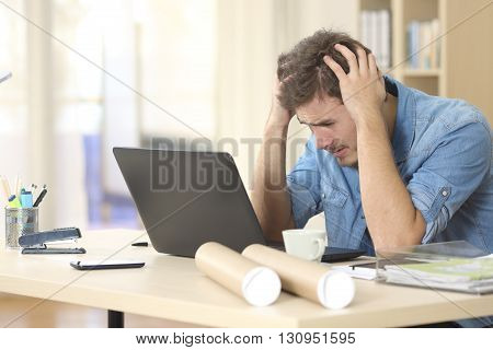 Sad freelance male worried watching bad news on line with a laptop on a desk at home or a little office