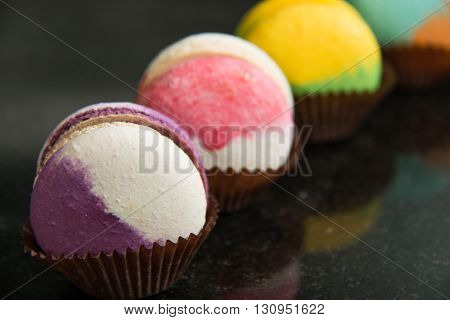 A assortment of colorful macaroon cookies on a paper cup
