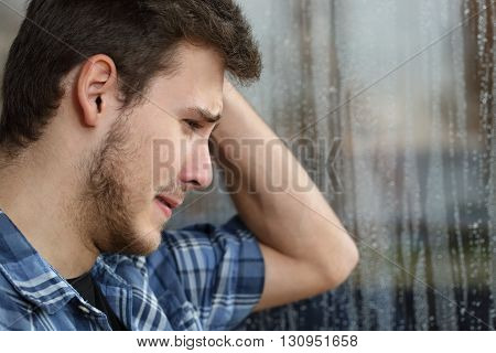 Side view of a sad man looking through window almost crying in a rainy day