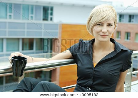 Businesswoman having break on office terrace outdoor drinking coffee.