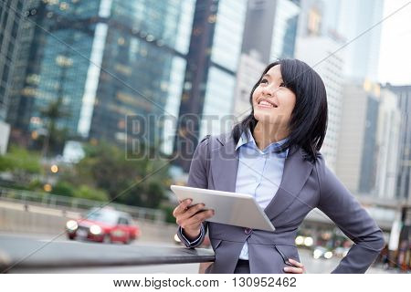Businesswoman hold with digital tablet and looking far away