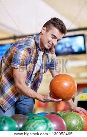 people, leisure, sport and entertainment concept - happy young man choosing ball in bowling club