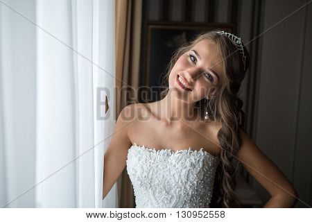 happy bride poses for a photograph in the bedroom by the window before the wedding. bride tilted her head to one side and smiling