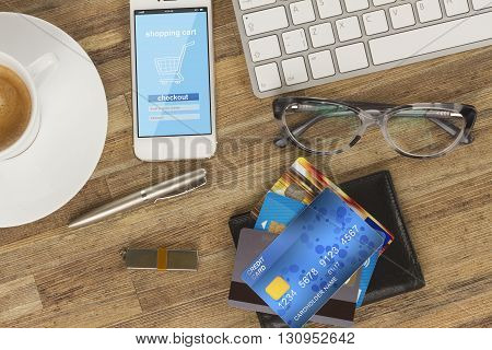 internet store page on mobile phone and wallet with plastic cards on work desktop