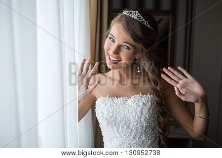 happy bride poses for a photograph in the bedroom by the window before the wedding