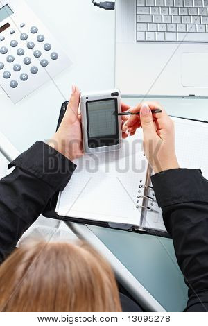 Female hand using touch screen handheld computer with stylus.