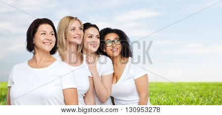 friendship, diverse, body positive and people concept - group of happy different size women in white t-shirts over blue sky and grass background