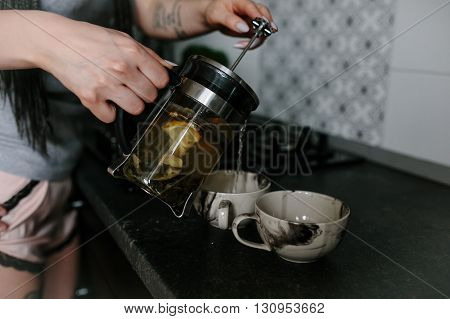 man and woman together making tea in the kitchen, close view
