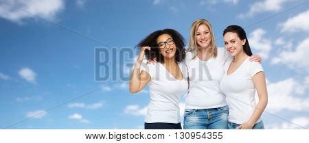 friendship, diverse, body positive and people concept - group of happy different size women in white t-shirts hugging over blue sky and clouds background