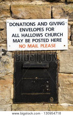 GEDLING ENGLAND - FEBRUARY 10: The donations box set into exterior wall of All Hallows Church Of England church. In Gedling Nottinghamshire England. On 10th February 2016.
