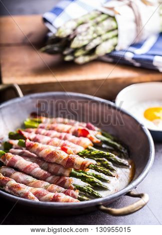 Asparagus. Asparagus and roll bacon. Grilled asparagus with rolled bacon and fried egg. Fried old pan full of rolled bacon with green asparagus and fried egg.