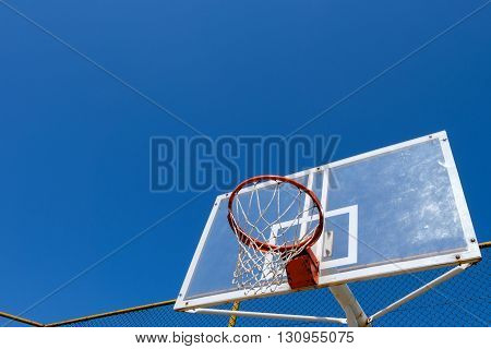 Outdoor basketball rim and backboard with blue sky