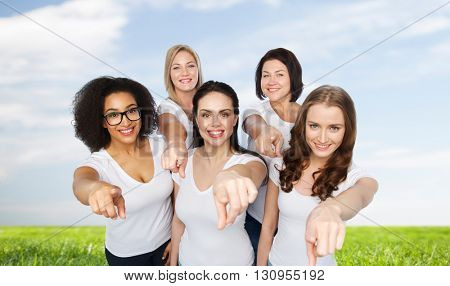 choice, friendship, body positive, gesture and people concept - group of happy different size women in white t-shirts pointing finger on you over blue sky and grass background