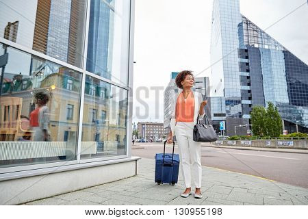 travel, business trip, people and tourism concept - happy young african american woman with travel bag on city street