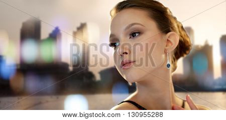 beauty, jewelry, people and luxury concept - face of beautiful young asian woman with earring over city silhouette and lights background