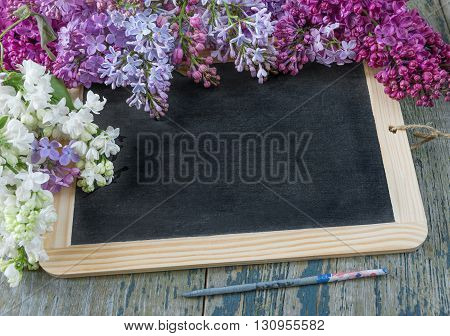 Flower border composed of lush multicolored bunches of lilac flowers around of empty black chalkboard on the old wooden background