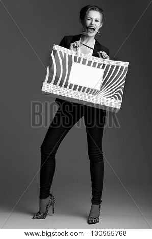 Woman With Big Shopping Bag Winking Against Grey Background