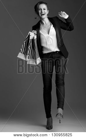 Cheerful Woman With Big Shopping Bags Against Grey Background