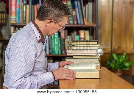 Senior Business Man Sitting At His Desk Full Of Books