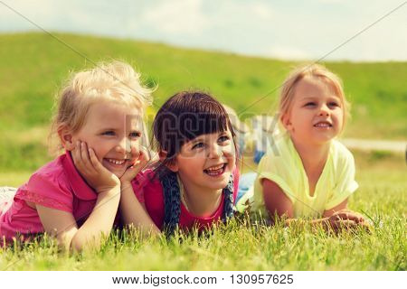 summer, childhood, leisure and people concept - group of happy kids lying on blanket or cover outdoors