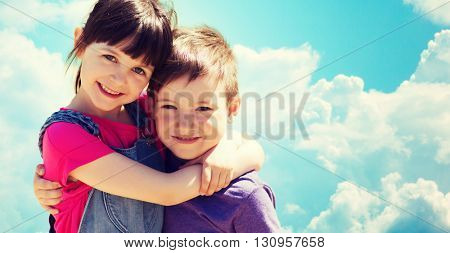 summer, childhood, family, friendship and people concept - two happy kids hugging over blue sky with clouds background