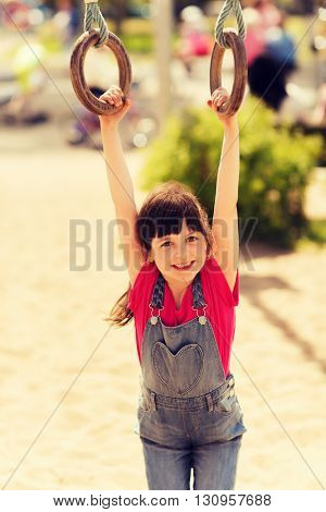 summer, childhood, leisure and people concept - happy little girl hanging on gymnastic rings at children playground